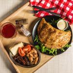 Pieróg pieczony gigant, obok wmisce pomidory, pomidory suszone, kurczak iser.