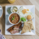 Śniadanie nabogato: jajka smażone, bekon, kiełbaski, fasolka pobretońsku, tosty.